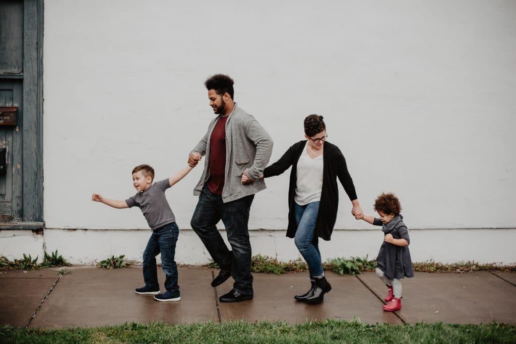 Família andando de mão dadas pela calçada.