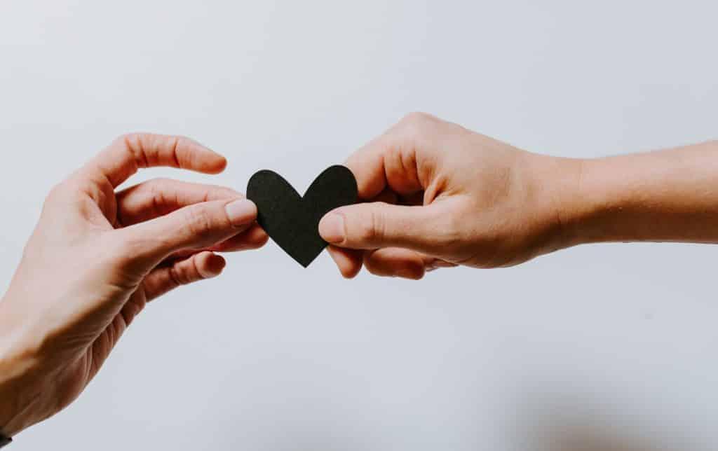 Duas pessoa segurando um coração de papel