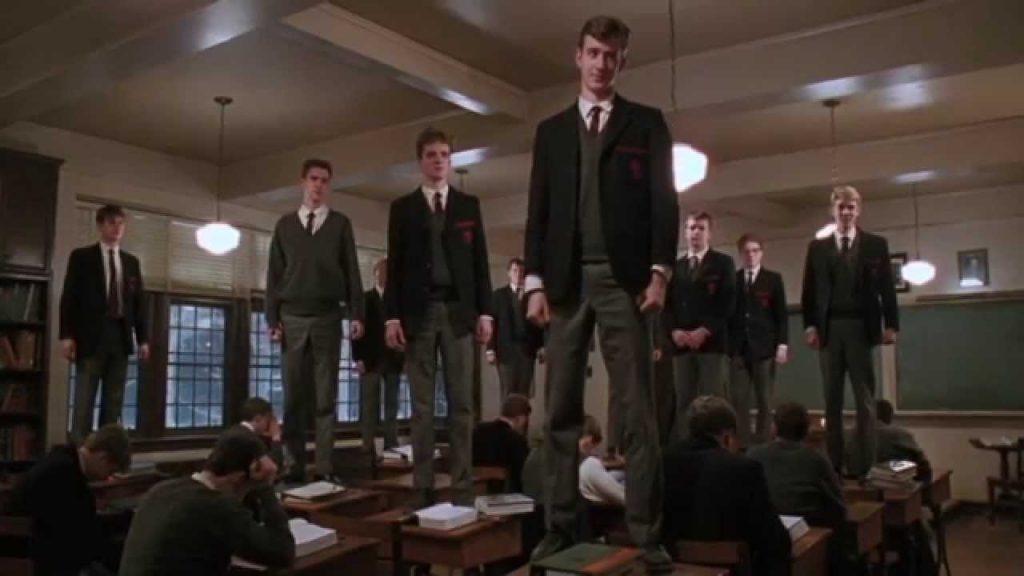 Alunos do professor John Keating em uma sala de aula, em pé sobre as mesas de estudo.