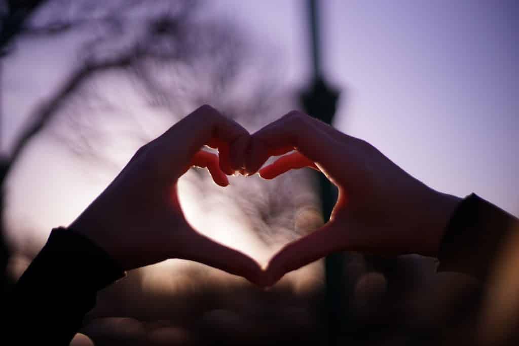 Pessoa formando com as mãos um coração