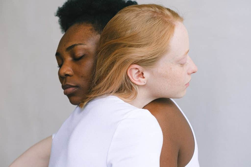Duas mulheres se abraçando com os olhos fechados e expressões serenas.