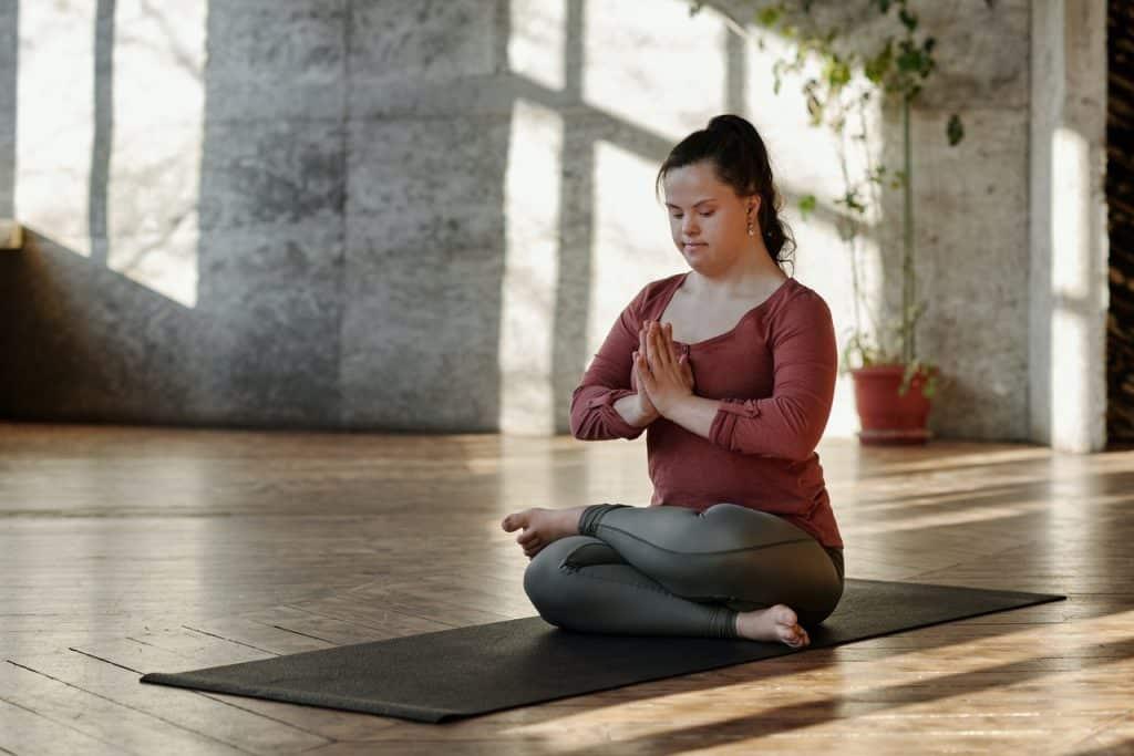 Mulher sentada. de pernas cruzadas e olhos fechados, meditando.
