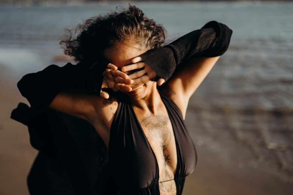 Mulher na praia com as mãos no rosto