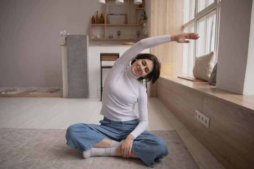 Mulher sorrindo em posição de meditação se alongando.