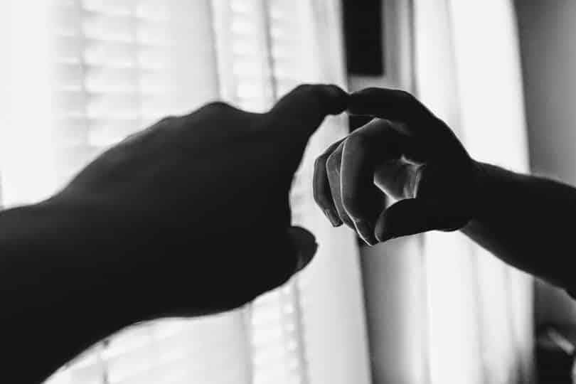 Mão de alguém tocando no relexo do vidro