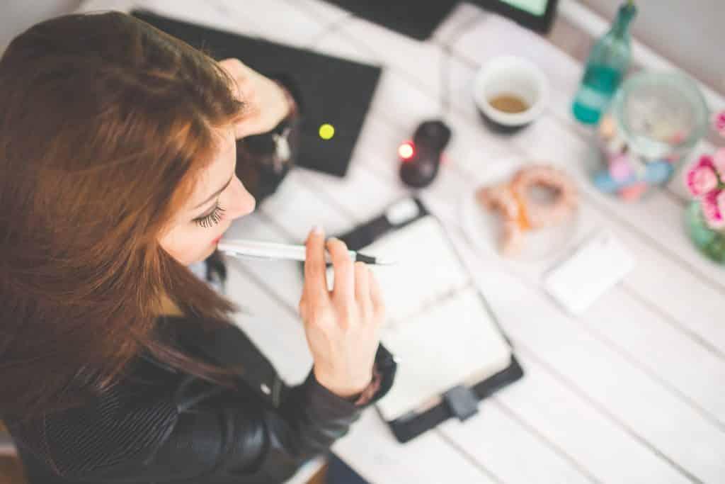 Mulher com uma caneta na boca em usa mesa de estudo