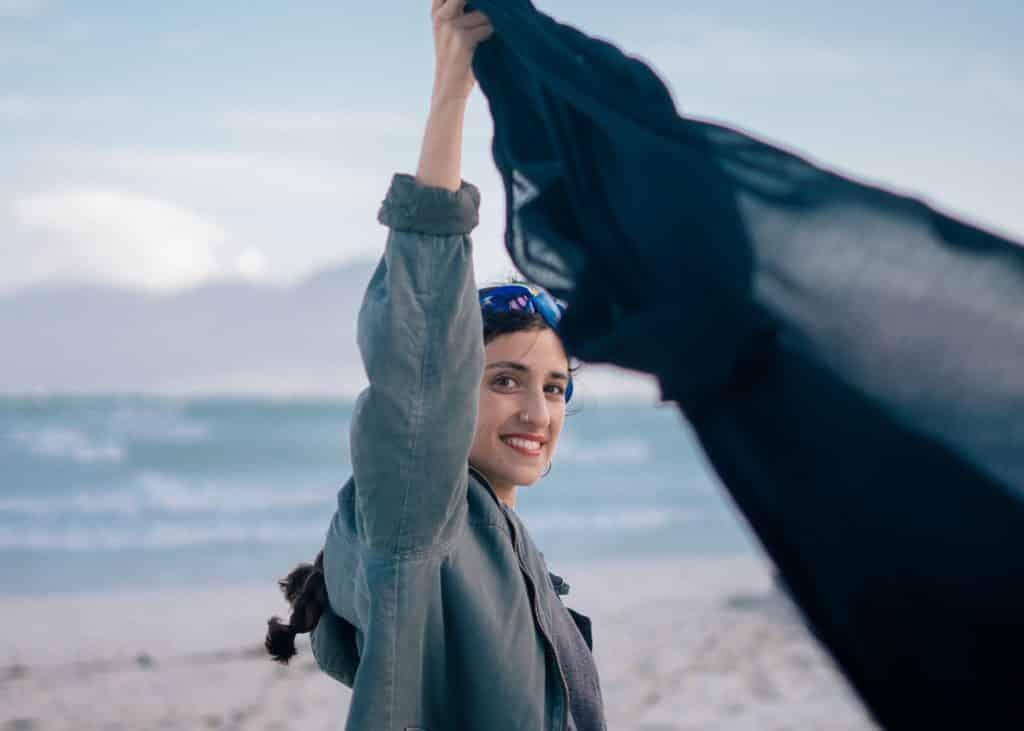 Mulher segurando um lenço na praia