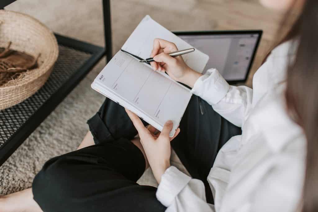 Mulher escrevendo em um caderno sentada no sofá