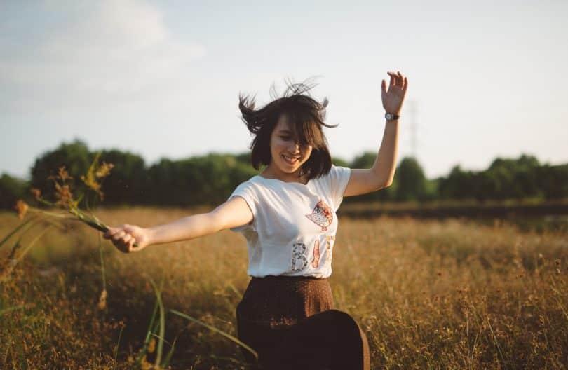 Mulher em um gramado sorrindo e pulando segurando um ramo de flor