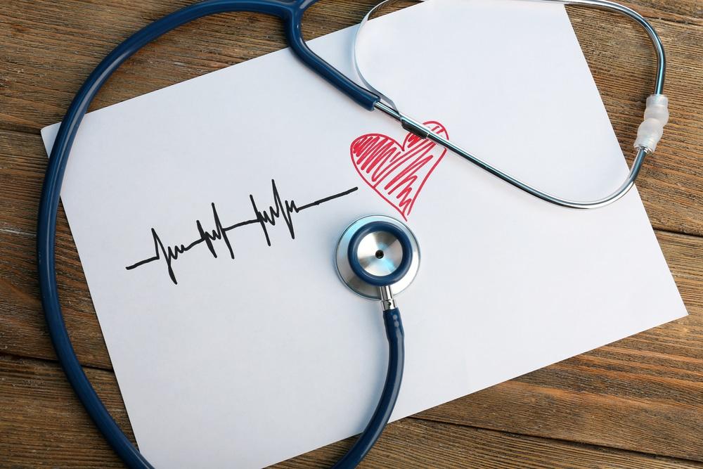Folha de papel branca com o desenho de um coração e os riscos dos batimentos cardíacos.