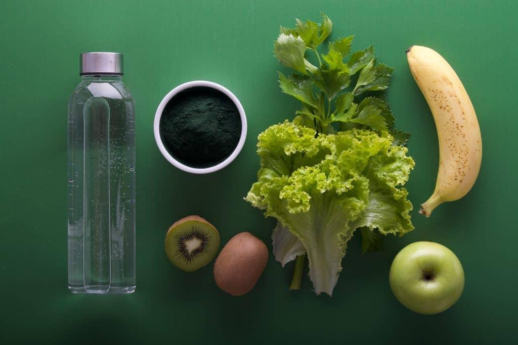 Diversas frutas ao lado de uma garrafa de água e de um potinho com tempero