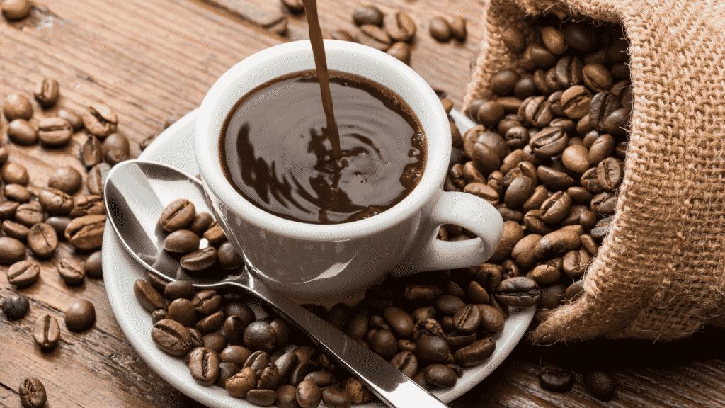 Xícara de café com grãos de café espalhados ao lado