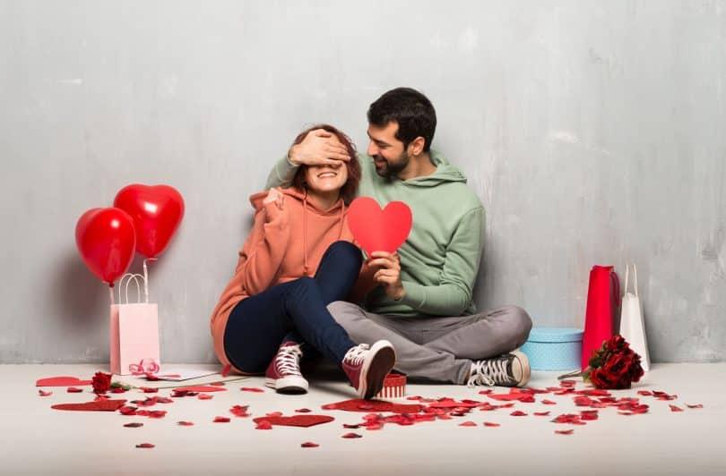 Casal no Dia dos Namorados segurando um símbolo de coração.