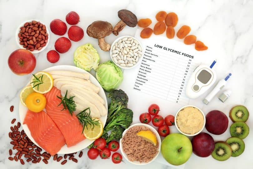 Alimentos e equipamentos para teste de açúcar no sangue e dispositivo de punção sobre a mesa branca.