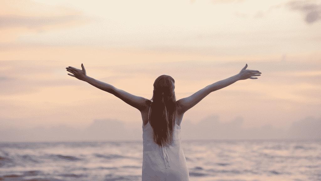 Mulher feliz com os braços abertos olhando para o mar