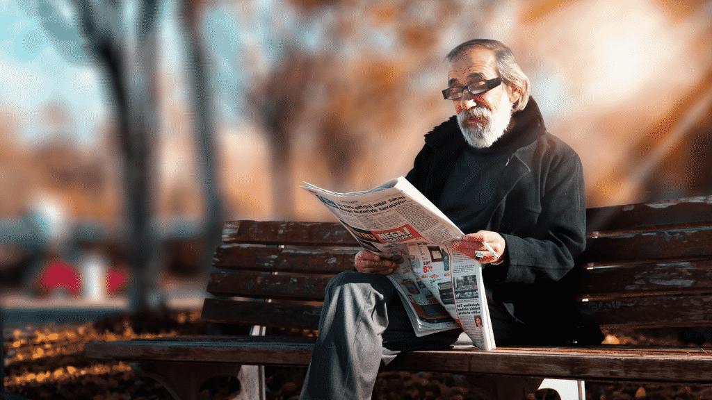 Idoso lendo jornal sentado no banco da praça