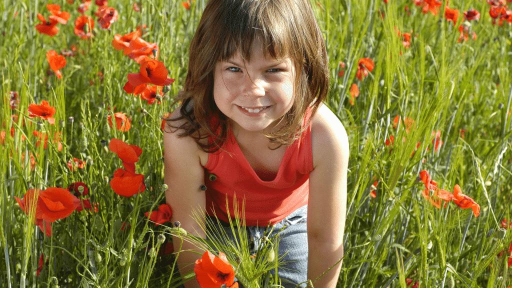Garota pequena brincando no campo de flores vermelhas