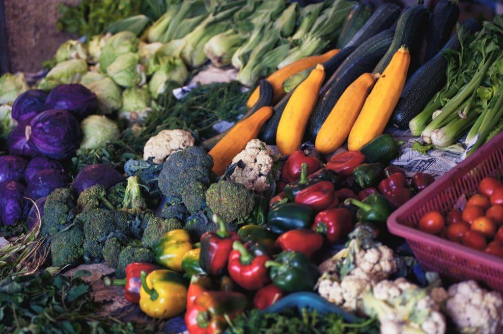 Banca de feira com diversos vegetais dispostos.