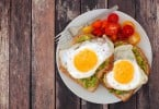 Healthy avocado egg open sandwiches on a plate with colorful tomatoes against a rustic wood background