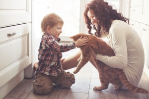 Mother with her baby playing with pet on the floor at the kitche