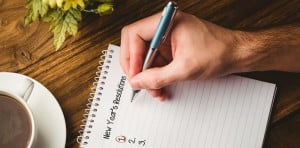 New years resolution list against cropped hand writing in book b