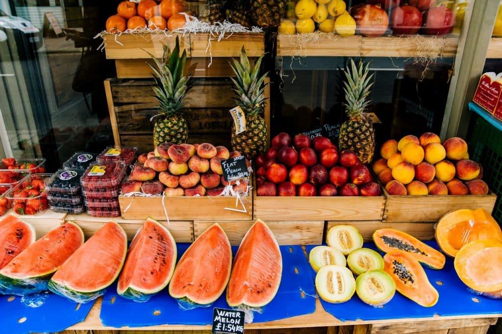 Uma banca de feira com vários tipos de frutas em cima.