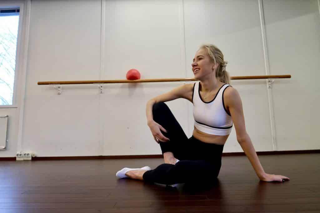 Menina loira com roupa de ginástica sentada no chão em uma sala de academia.