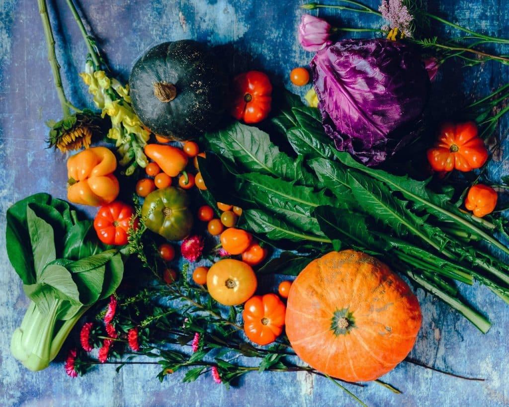 Mesa azul com vários tipos de legumes em cima.