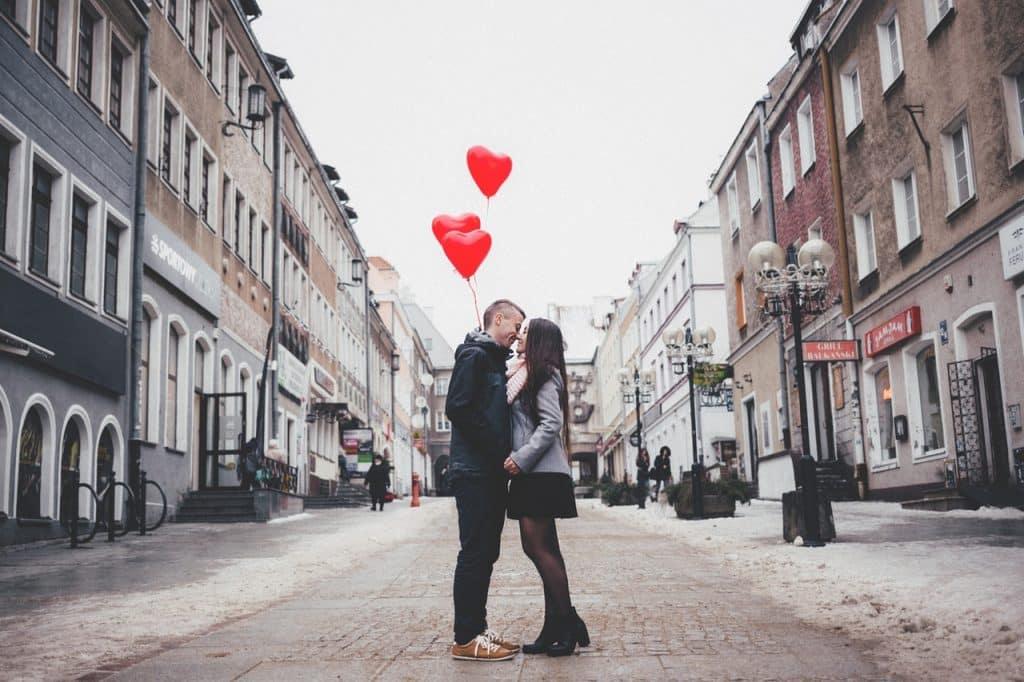 Casal segurando balões em formato de coração enquanto se beijam no meio da rua.