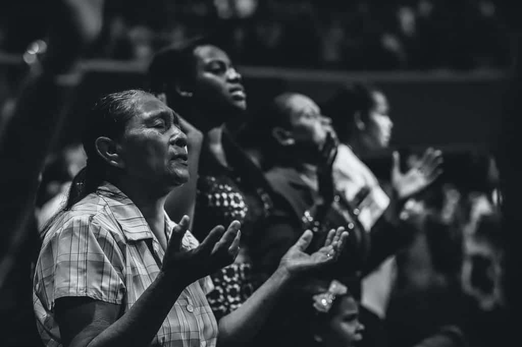 Foto em preto e branco de pessoas rezando