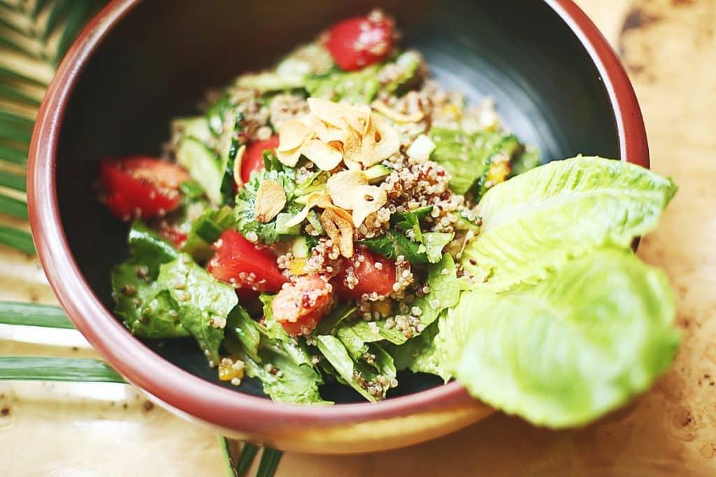 Uma tupperware com verduras e salada.