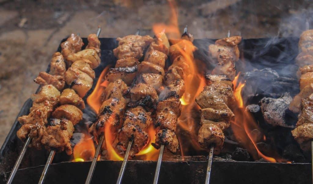 Sete espetinhos de carne sobre a churrasqueira.