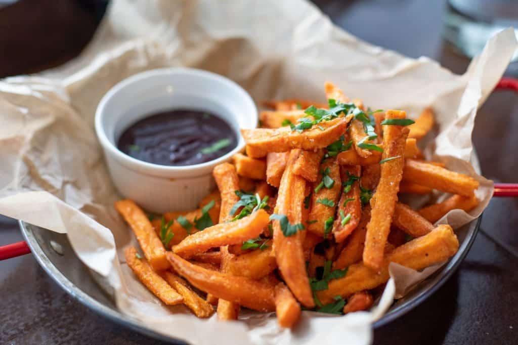 Uma porção de batata frita com acompanhamento.