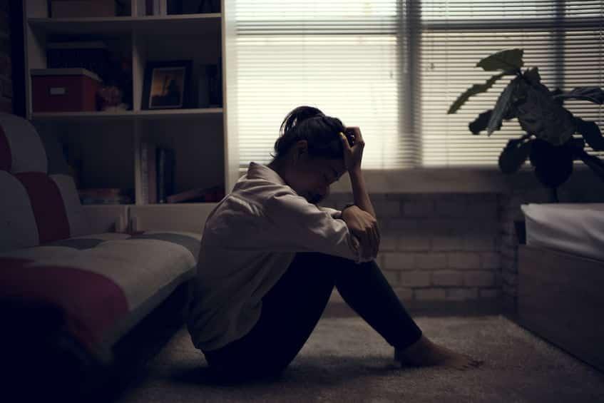 Mulher sentada no chão da sala, com as mãos sobre o rosto, chorando.