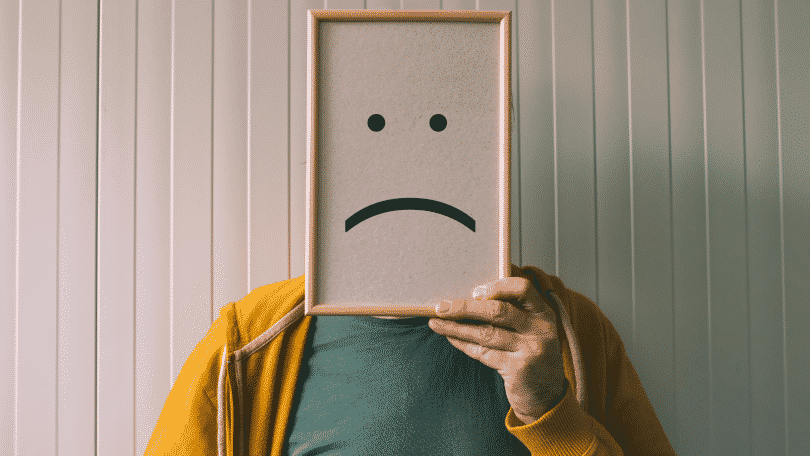 Pessoa com um quadro na frente do rostocontendo uma carinha triste