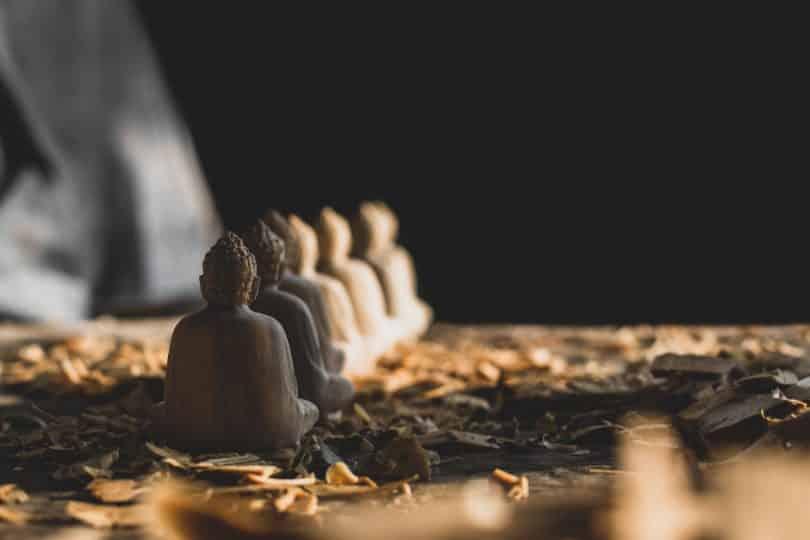 Seis estátuas de madeira de Buda em fila.