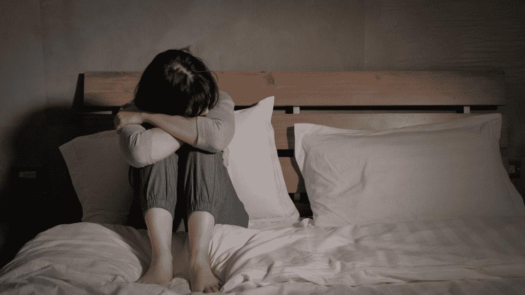 Mulher depressiva abraçando os joelhos.