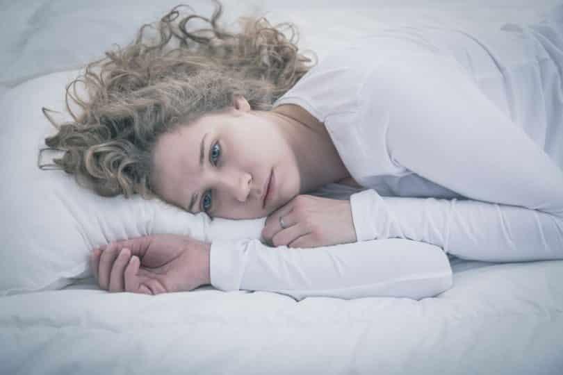 Mulher deitada na cama com olhar triste.