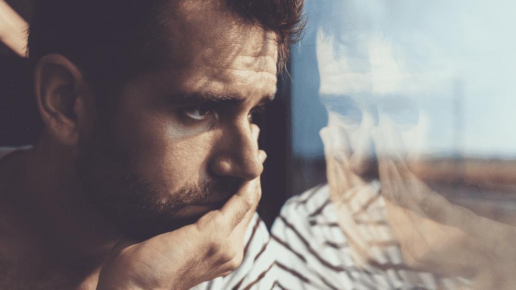 Homem triste olhando pensativo pela janela.