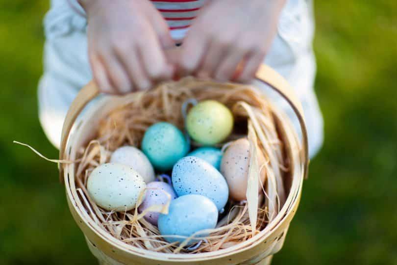 Criança segurando uma cesta com pequenos ovos de páscoa.