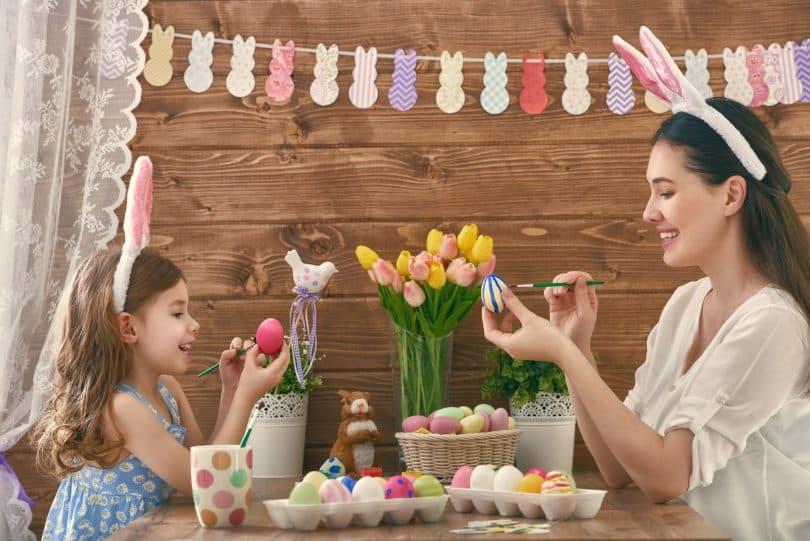 Uma mãe e sua filha usando orelhas de coelho pintando ovos de Páscoa.