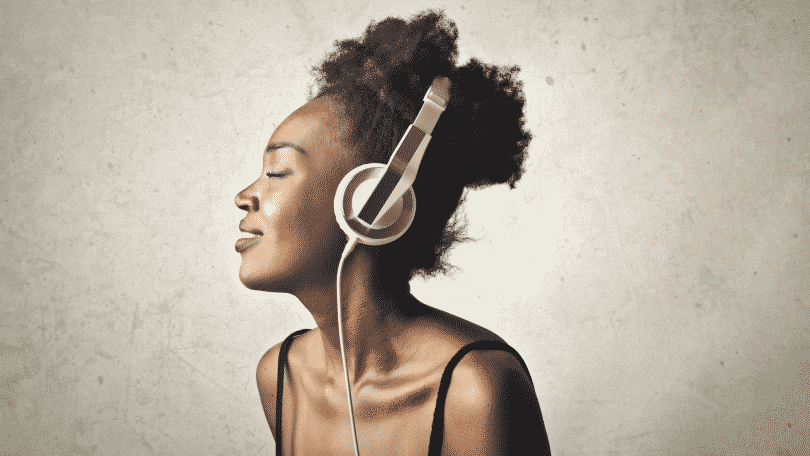 Mulher de olhos fechados ouvindo música com fone de ouvido