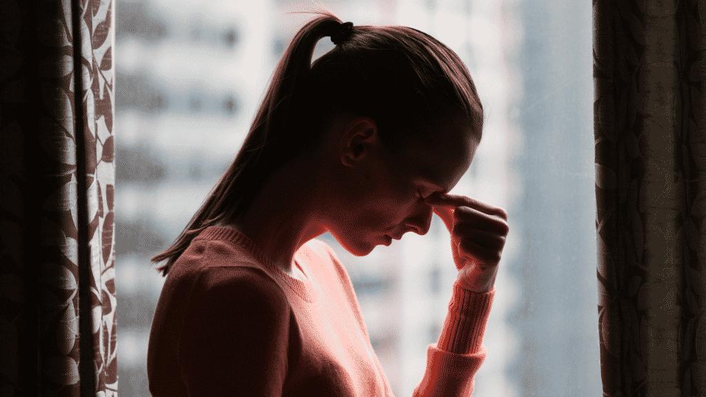 mulher estressada pressionando o cenho com os dedos