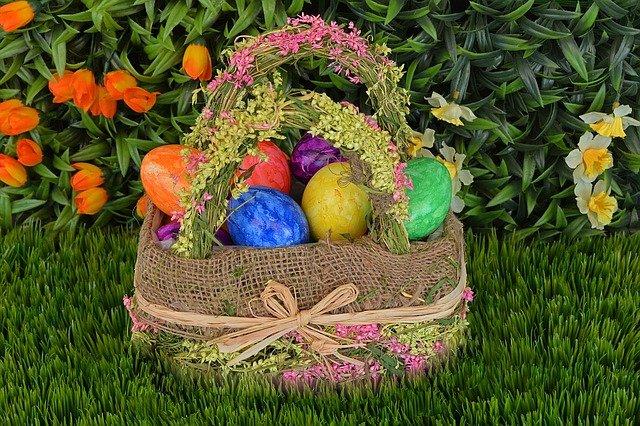 Uma cesta com ovos de Páscoa em um jardim.