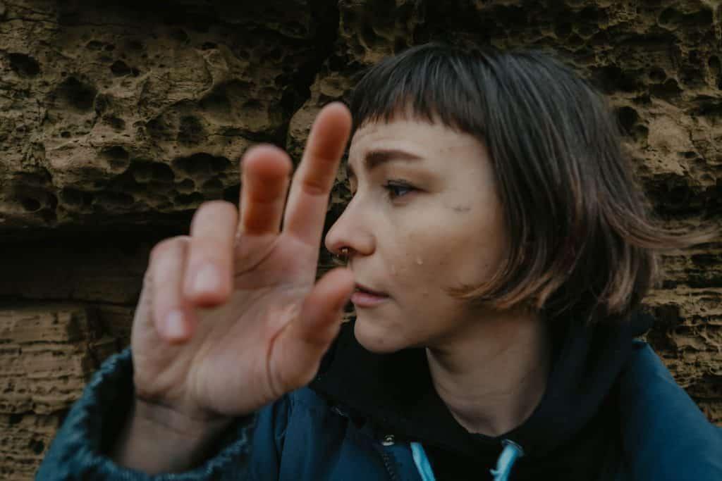 Mulher olhando para o lado com tristeza com sua mão ao lado do rosto