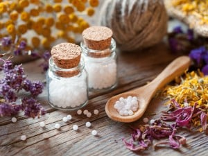 Bottles Of Homeopathy Globules, Wooden Spoon And Dry Healthy Her