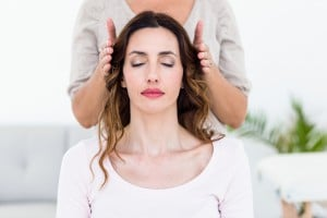 Calm woman receiving reiki treatment on white background