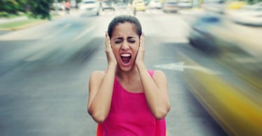 Portrait of woman standing still in the middle of a street with cars passing by fast screaming stressed and frustrated