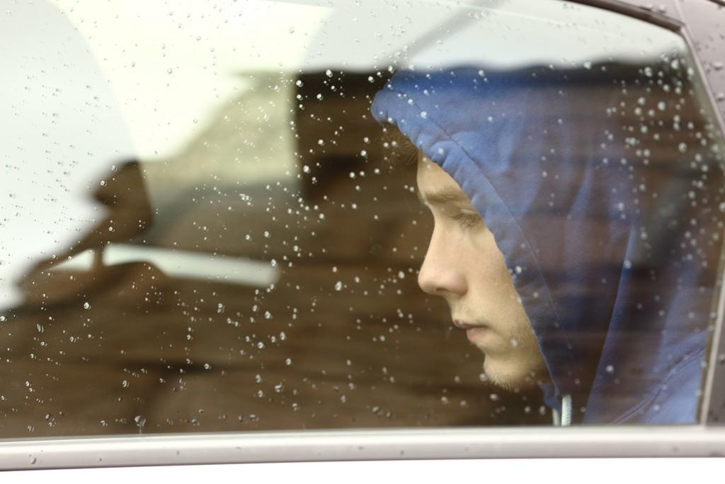 Menino triste dentro de um carro.