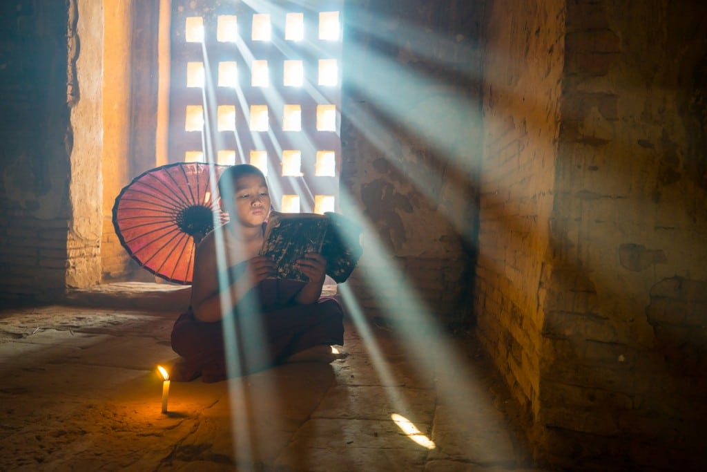 BAGAN, MYANMAR - DEC 12, 2015: Unidentified Buddhism neophyte prays in Buddihist temple on December 12, 2015 in Bagan, Myanmar. Southeast Asian neophyte praying in a Buddihist temple